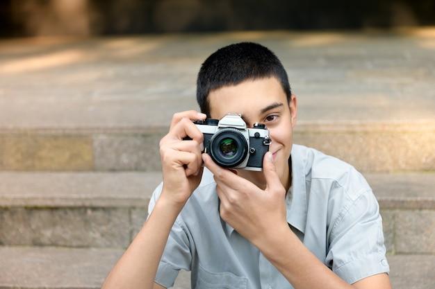 Jeune adolescent photographiant le spectateur
