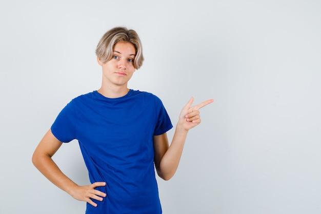 Jeune adolescent pointant vers le coin supérieur droit en t-shirt bleu et regardant hésitant, vue de face.