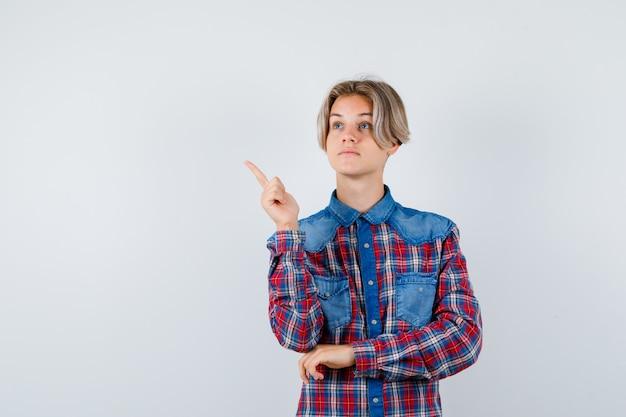 Jeune adolescent pointant vers le coin supérieur gauche