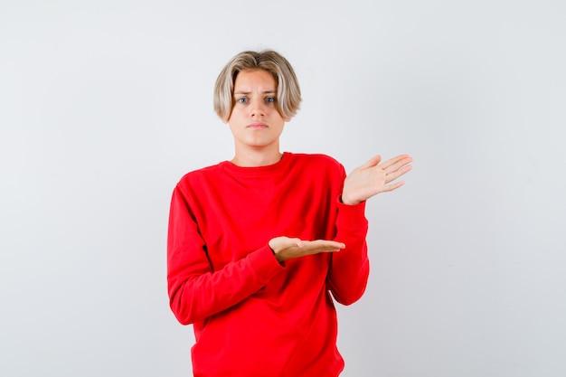 Jeune adolescent en pull rouge faisant semblant de montrer quelque chose et ayant l'air désemparé, vue de face.