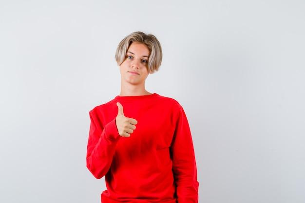 Jeune adolescent en pull rouge montrant le pouce vers le haut et l'air satisfait, vue de face.
