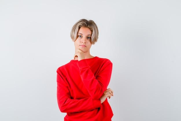 Jeune adolescent en pull rouge soutenant le menton à portée de main et semblant sensible, vue de face.