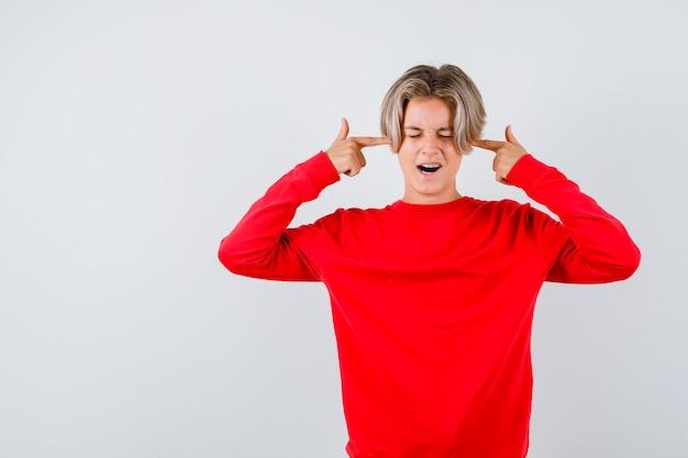 Jeune adolescent qui se bouche les oreilles avec les doigts dans un pull rouge et a l'air irrité. vue de face.