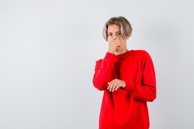 Jeune adolescent qui sent quelque chose d'affreux, se pince le nez dans un pull rouge et a l'air dégoûté, vue de face.