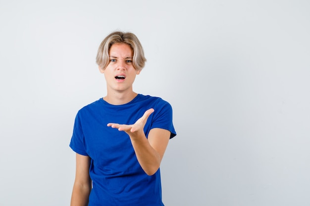 Jeune adolescent qui tend la main à l'avant en t-shirt bleu et a l'air perplexe. vue de face.