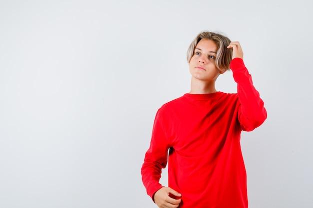 Jeune adolescent regardant loin tout en se grattant la tête en pull rouge et l'air pensif. vue de face.