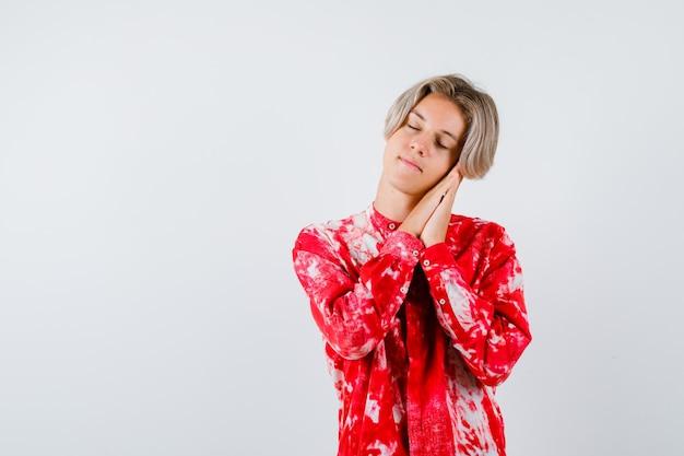 Jeune adolescent s'appuyant sur les paumes comme oreiller en chemise et ayant l'air endormi, vue de face.