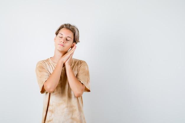 Jeune adolescent s'appuyant sur les paumes comme oreiller en t-shirt et ayant l'air endormi. vue de face.
