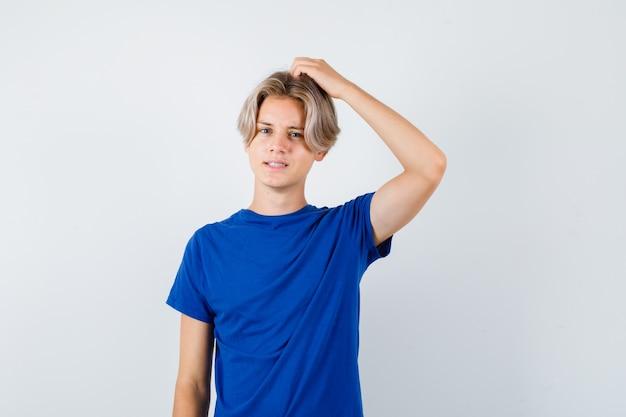 Jeune adolescent se grattant la tête en t-shirt bleu et ayant l'air oublieux. vue de face.