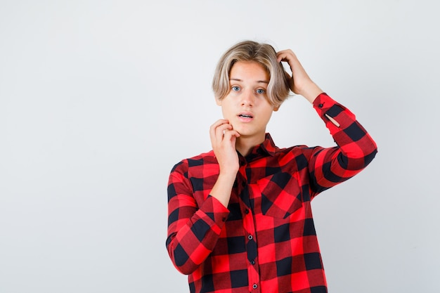 Jeune adolescent se grattant la tête, touchant sa mâchoire en chemise à carreaux et ayant l'air perplexe. vue de face.