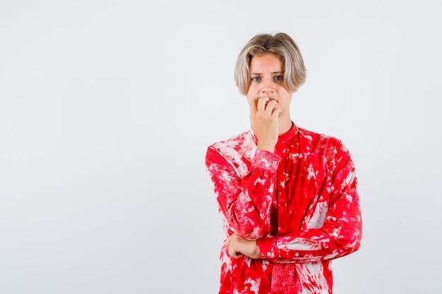Jeune adolescent se rongeant les ongles émotionnellement en chemise et ayant l'air anxieux. vue de face.