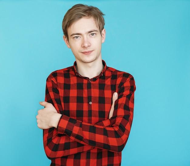 Jeune adolescent de sexe masculin en chemise rouge sur fond bleu
