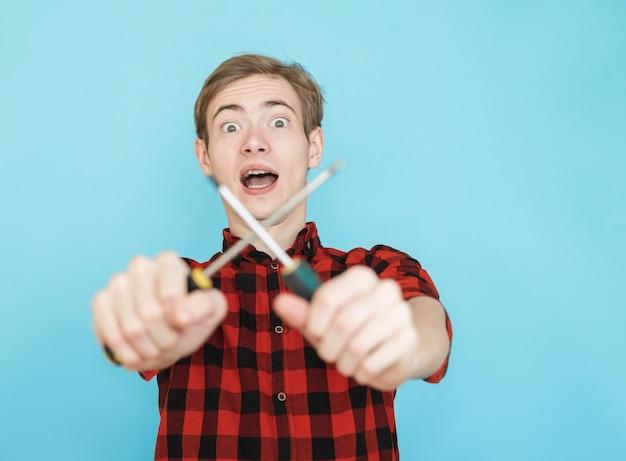 Jeune adolescent de sexe masculin émotionnel souriant en chemise rouge sur fond bleu avec tournevis