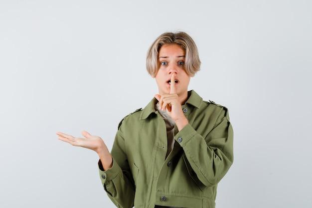 Jeune adolescent en t-shirt affichant et faisant un geste de silence