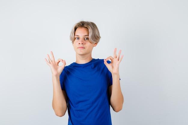 Jeune adolescent en t-shirt bleu montrant un geste correct et l'air étonné, vue de face.