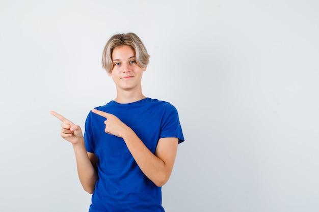 Jeune adolescent en t-shirt bleu pointant vers la gauche et regardant jolly , vue de face.