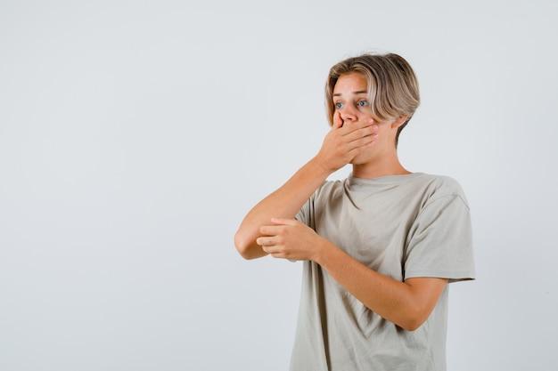 Jeune adolescent en t-shirt avec la main sur la bouche