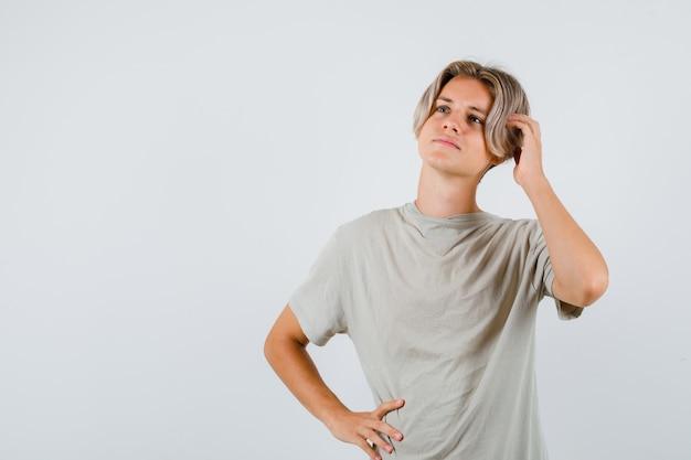 Jeune adolescent en t-shirt avec la main sur la tête