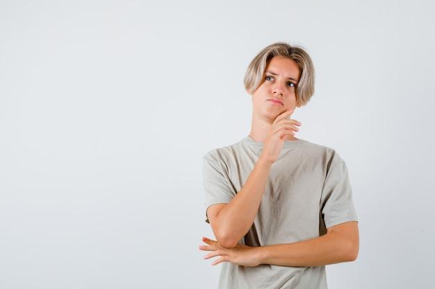 Jeune adolescent en t-shirt touchant le menton tout en levant les yeux et en ayant l'air pensif