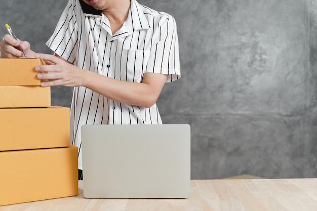 Jeune adolescent en tant qu'indépendant travaillant avec un ordinateur portable et emballage d'une boîte à colis postal dans le salon à la maison