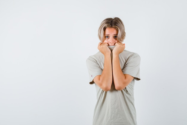 Jeune adolescent tirant le col sur le visage en t-shirt et ayant l'air effrayé. vue de face.