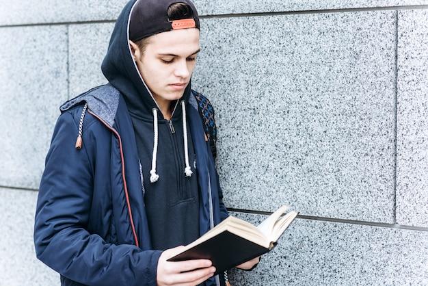Jeune adolescent en train de lire un livre