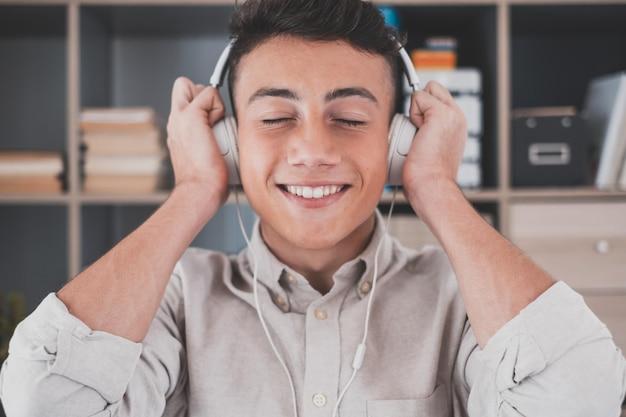 Jeune adolescent tranquille et insouciant à la maison, portant des écouteurs sans fil modernes, écoutant de la musique classique préférée en ligne, se sentant paisible et conscient seul dans le salon.