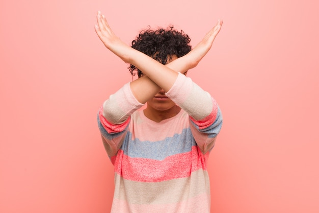 Jeune adolescente afro-américaine mixte gardant les deux bras croisés, déni.