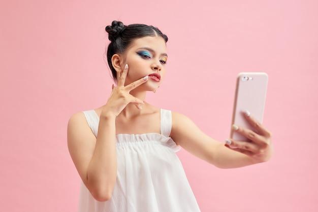 Jeune adolescente asiatique sur fond rose isolé faisant un selfie