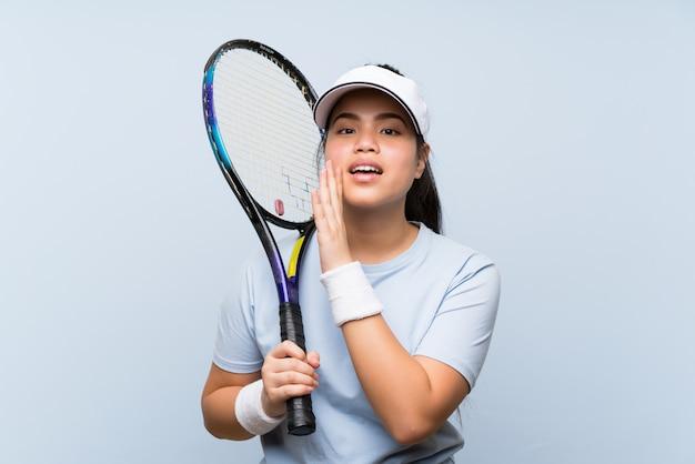 Jeune adolescente asiatique jouant au tennis en chuchotant quelque chose