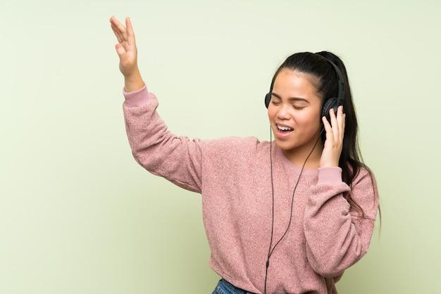 Jeune adolescente asiatique sur mur vert isolé, écouter de la musique avec des écouteurs