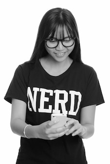 Jeune adolescente asiatique ringard avec des lunettes isolé contre un mur blanc en noir et blanc