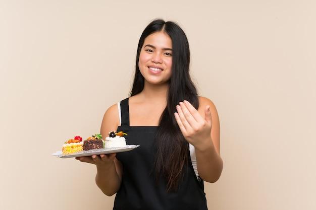 Jeune adolescente asiatique tenant beaucoup de mini gâteaux différents sur un mur isolé invitant à venir avec la main. heureux que tu sois venu