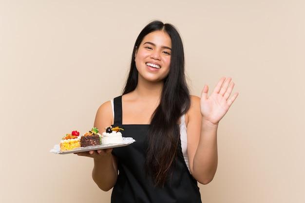 Jeune adolescente asiatique tenant beaucoup de mini gâteaux différents mur isolé saluant avec main avec expression heureuse