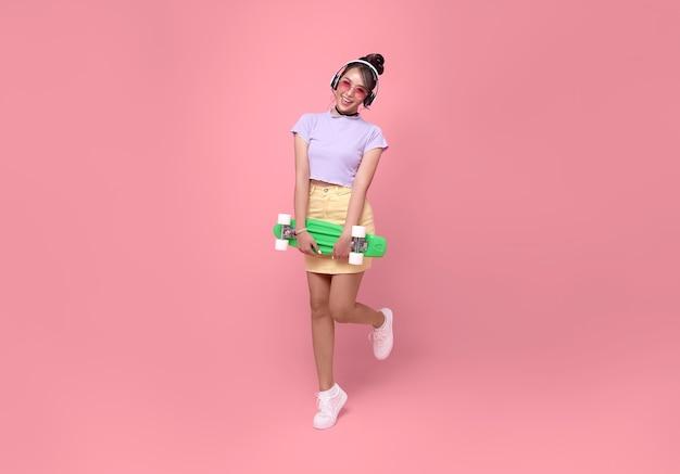 Jeune adolescente asiatique tenant une planche à roulettes avec des écouteurs sans fil, écoutant de la musique sur fond rose.