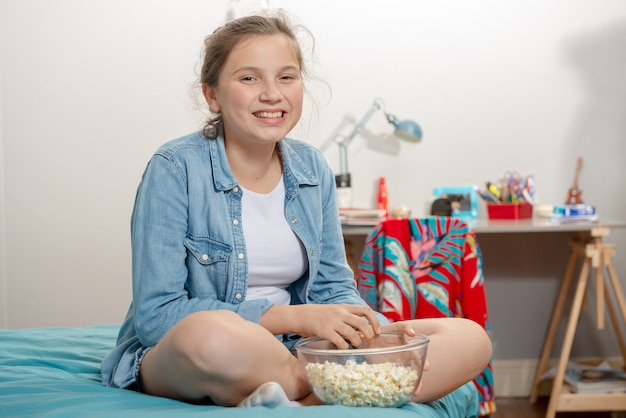 Jeune adolescente assise sur le lit en train de manger du pop-corn