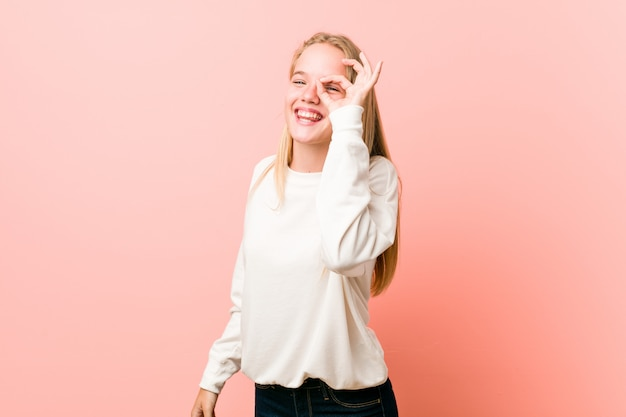Jeune adolescente blonde excitée en gardant les yeux du geste ok.