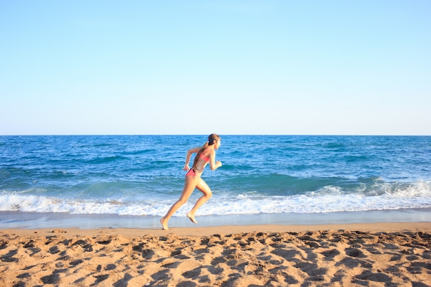 Jeune adolescente court sur la plage le long de la mer
