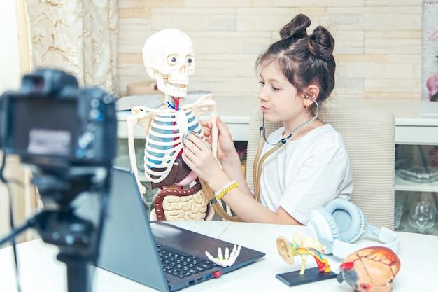 Une jeune adolescente enregistre un blog vidéo à la maison. elle parle aux abonnés de l'anatomie humaine. passe-temps inhabituel.