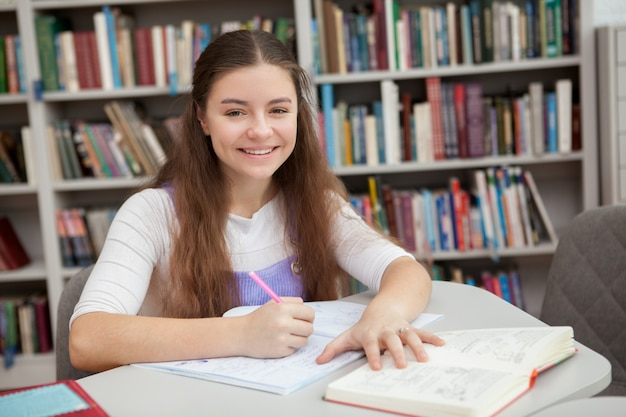 Jeune adolescente étudie à la bibliothèque