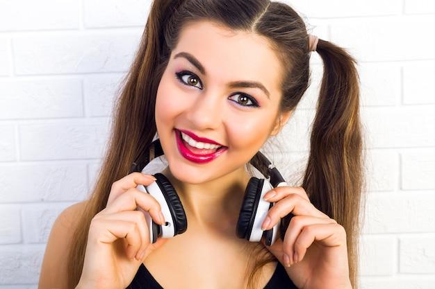 Jeune adolescente ludique heureuse avec deux queues de cheval s'amusant et souriant, écoutant sa musique préférée sur de grands écouteurs blancs, portant une tenue noire élégante et un maquillage lumineux, mur urbain