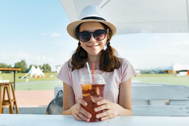 Jeune adolescente en lunettes de soleil chapeau souriant et buvant un cocktail de baies fraîches