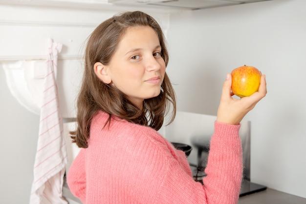Jeune adolescente mange une pomme