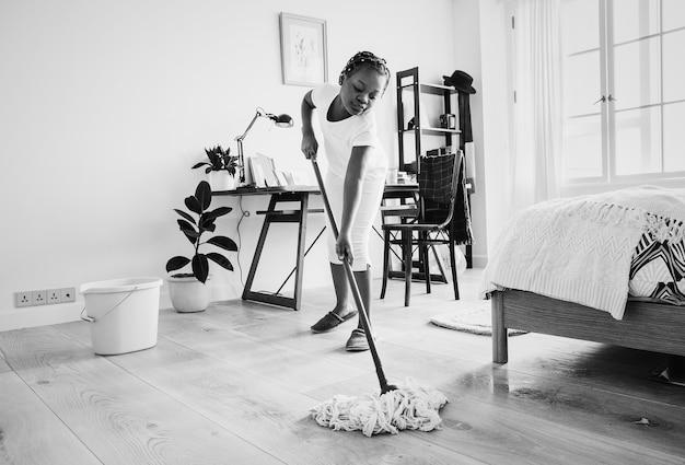 Jeune adolescente qui balaie le sol