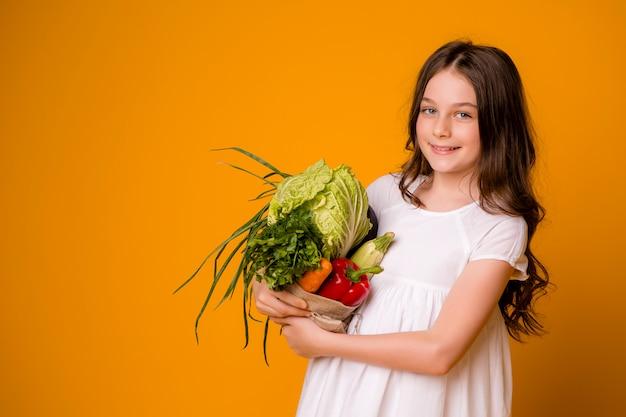 Jeune adolescente avec un sac de légumes