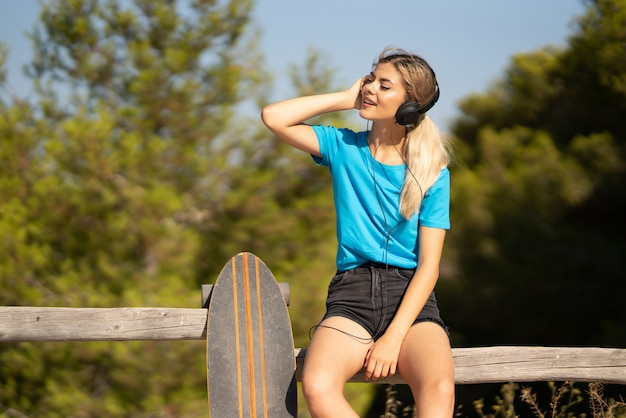 Jeune adolescente avec skate en écoutant de la musique avec des écouteurs à l'extérieur