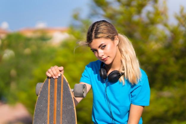 Jeune adolescente avec skate en plein air