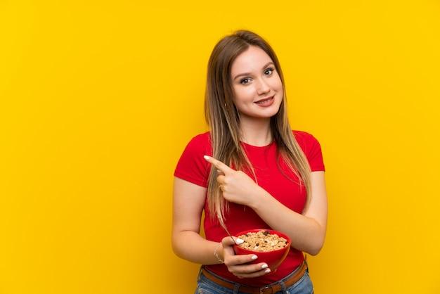 Jeune adolescente tenant un bol de céréales pointant sur le côté pour présenter un produit