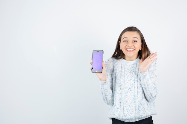 Jeune adolescente tenant le smartphone sur fond blanc.