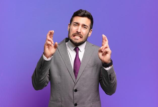 Jeune adulte bel homme d'affaires croisant les doigts avec anxiété et espérant bonne chance avec un regard inquiet